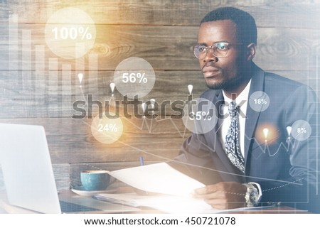 Double exposure of African student in suit and glasses sitting in front of laptop with dreamy pensive look, thinking of his bright future as a successful man while working on diploma. Interest rates - stock photo