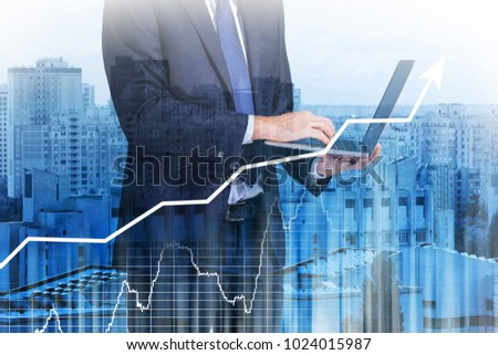 Double exposure of broker with laptop, stock exchange charts and cityscape view