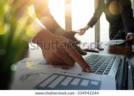 double exposure of business documents on office table with modern laptop computer and digital business strategy diagram and two colleagues discussing data in the background with plant in foreground - stock photo