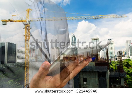 Double exposure of business engineer Hold Wireless Digital Tablet PC and abstract city as Construction industrial concept