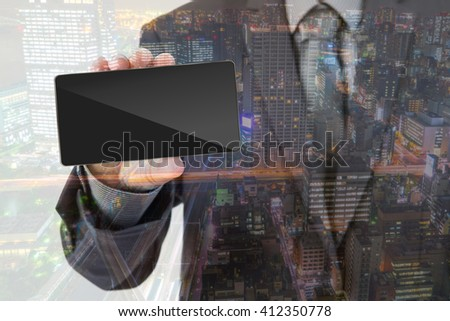 Double exposure of Business man Hand holding mobile smart phone with cityscape - stock photo