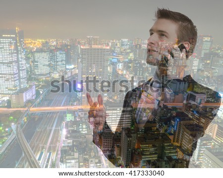 Double exposure of Business man using mobile phone with cityscape
