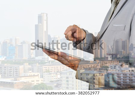 Double Exposure of Business Man using Mobile Tablet and Modern Building in the City