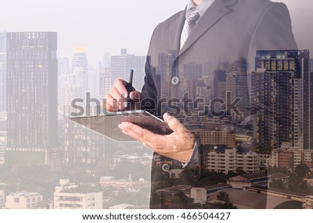 Double exposure of Business man working with a digital tablet with cityscape blurred building background, Business Trading concept