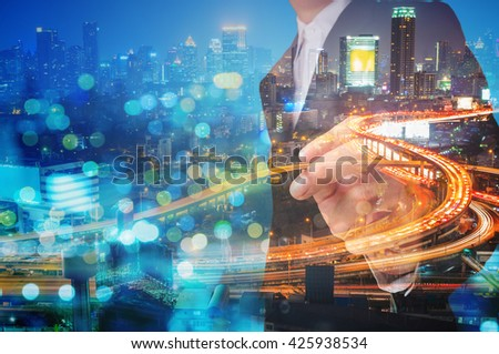 Double Exposure of Businessman draw Something with City Traffic Scene at Night and Glass decorated Building, Business concept