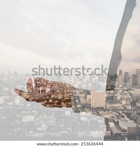 Double exposure of businessman hand and city background - stock photo