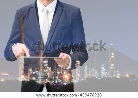 Double exposure of businessman hand hold tablet, oil refinery industry plant, Petroleum energy concept