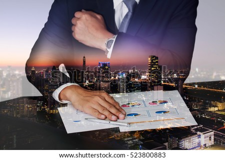 Double exposure of businessman hand put on the chart document, cityscape, urban and street in the night or twilight as business, meeting and analysis concept.