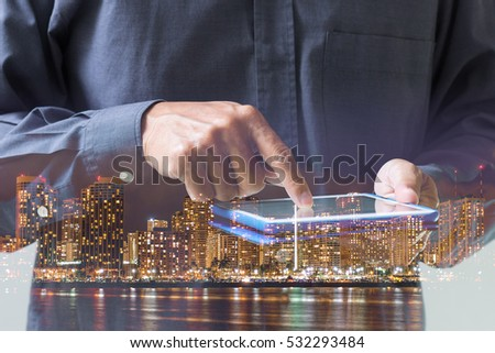 Double exposure of businessman hand touching digital tablet over night cityscape