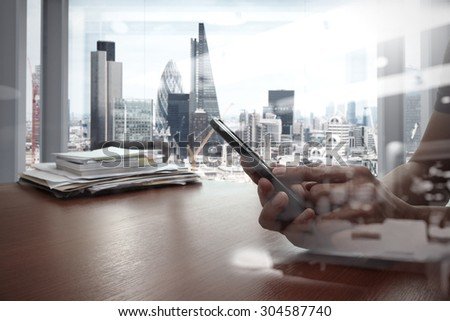 double exposure of businessman hand use smart phone with office workspace - stock photo