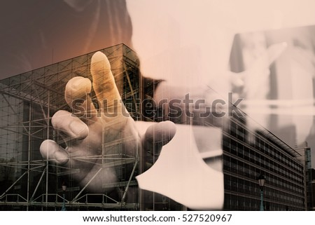 Double exposure of businessman hand using mobile payments online shopping,omni channel,laptop computer on wooden desk,London architecture buildings