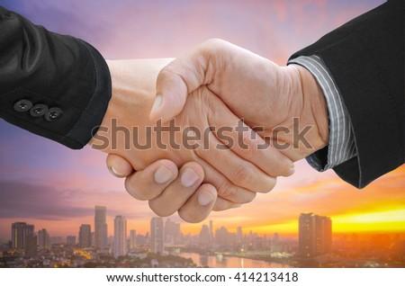 Double exposure of businessman handshake on blurred cityscape background. - stock photo