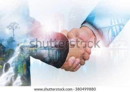 Double exposure of businessman handshake on blurred cityscape background,Green Business. - stock photo