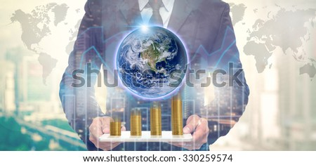 Double exposure of Businessman holding the tablet with earth and stack of golden coins on Trading graph on the cityscape at night and world map background,Elements of this image furnished by NASA - stock photo