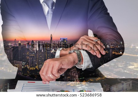Double exposure of businessman look the watch, cityscape, urban and street in the night or twilight as appointment and business concept.