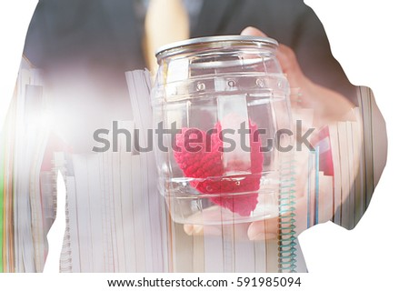 Double exposure of Businessman showing compassion holding red heart in jars, stack of book isolated on white background