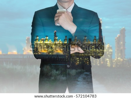 Double exposure of businessman stand up and think idea about business, electric generating factory industry in the night as business, energy and thoughtful concept.