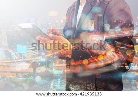 Double Exposure of Businessman use Tablet and Traffic on Highway in the City at Night