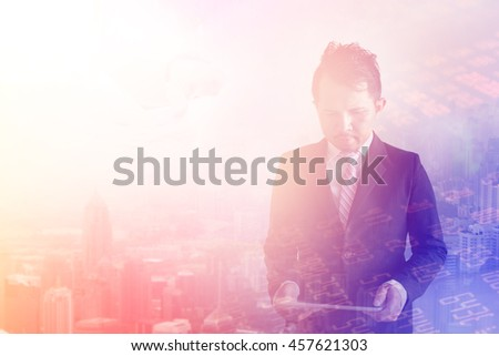 Double exposure of businessman using digital tablet with city landscape background,