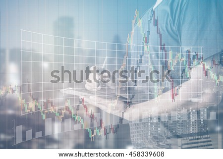Double exposure of businessman using digital tablet with city landscape blurred background.with stock chart, investment concept.
