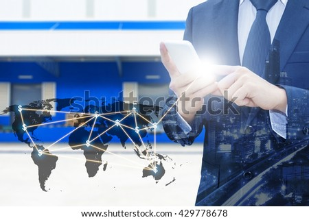 Double exposure of businessman using smart phone network connection world map by NASA and city of business , blurred cargo distribution warehouse, international transportation trading business concept