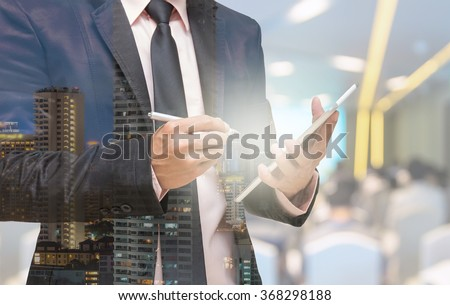 Double exposure of Businessman using the tablet on the Abstract blurred photo of conference hall or seminar room with attendee background - stock photo