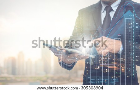 Double exposure of businessman using the tablet with cityscape and financial graph on blurred building background, Business Trading concept - stock photo