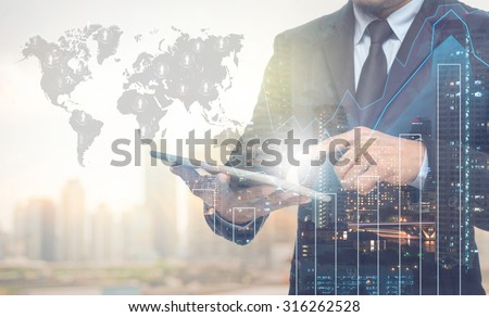 Double exposure of businessman using the tablet with cityscape and financial graph on blurred building with world map and people logo background, Elements of this image furnished by NASA - stock photo