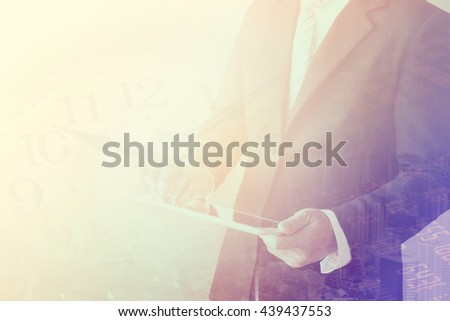 Double exposure of businessman using the tablet with cityscape,finance and stock market
