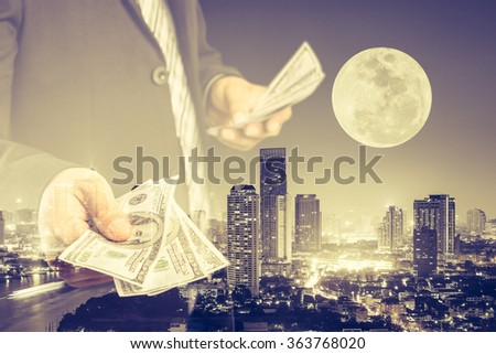 Double exposure of Businessman with money in hand with cityscape blurred building background, success and profitable business concepts. (Elements of this image furnished by NASA) - stock photo