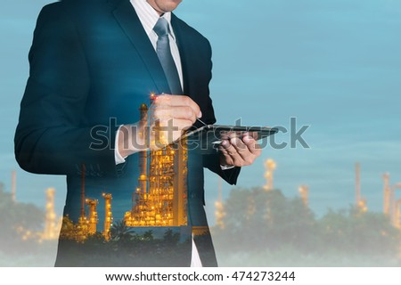Double exposure of businessman working with tablet and oil refinery industry plant at night as Energy and Technology concept.