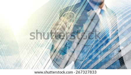 Double exposure of businessman writing the idea with cityscape building glass