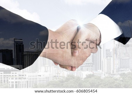 Double exposure of 2 businessmen shaking hands with city in background.