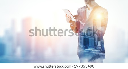 Double exposure of city and business man using digital tablet  - stock photo