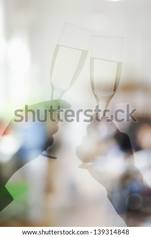 Double exposure of couple toasting with champagne flutes - stock photo