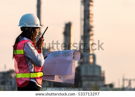 Double exposure of Engineer with safety helmet in front of Oil refinery and gas industry - refinery at sunset background, Business Insustrail concept