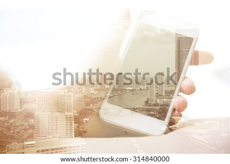 Double exposure of hand with mobile phone and bangkok cityscape in the background - stock photo