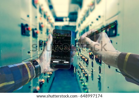 Double exposure of  hand working stock trading with smart phone in switch gearl room of oil and gas platform or plant industrial for monitor process, business and industry concept.