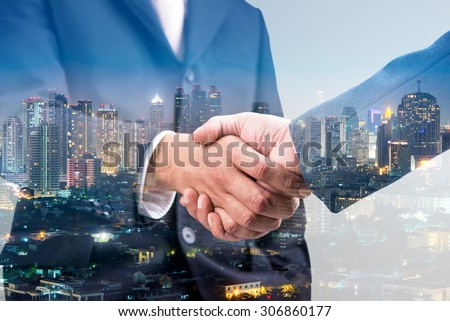Double exposure of handshake and city