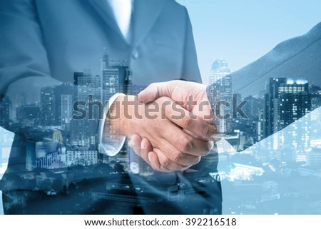Double exposure of handshake and city night, blue tone  - stock photo