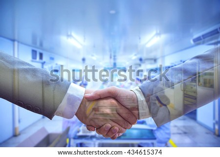 Double exposure of handshake and Manufacturing factory blur background. The business dealings Concept
