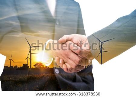Double exposure of handshake and silhouette of wind turbine at sunset - stock photo