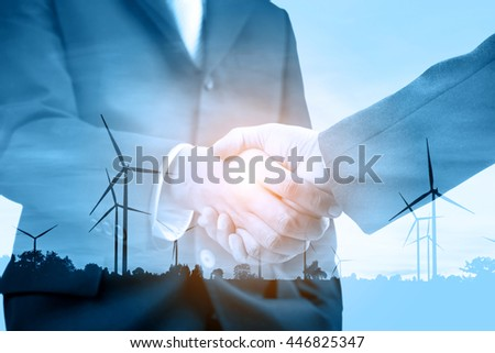 Double exposure of handshake and silhouette of wind turbine at sunset