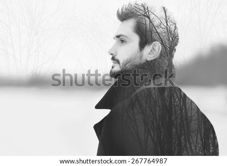 Double exposure of handsome elegant bearded man in profile pensive looks into the distance, black and white photo
