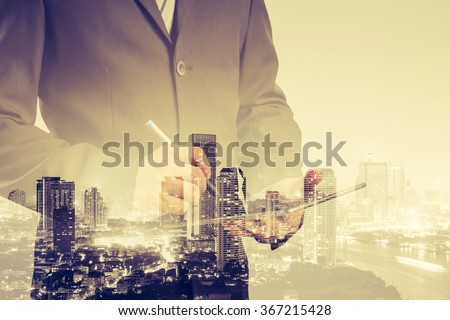Double exposure of success businessman using digital tablet with city landscape background - stock photo