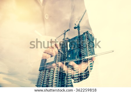 Double exposure of success businessman using digital tablet with Construction site with crane and building - stock photo