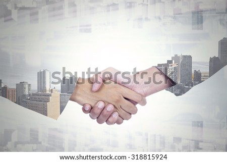 Double exposure of two businesspeople shaking hands with office building background - stock photo