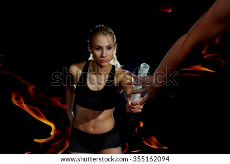 double exposure of woman and fire in background, athletic runners passing baton in relay race - stock photo