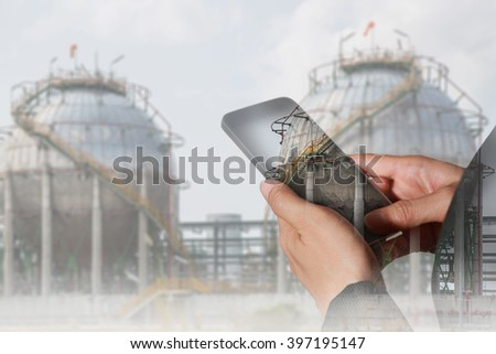 Double exposure of woman hand hold and touch screen smart phone, tablet,cellphone and Energy oil refinery Factory at daytime as Energy and Technology concept.
