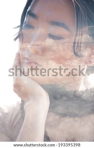 Double exposure portrait of attractive asian woman combined with photographs of clouds shot from a plane - stock photo